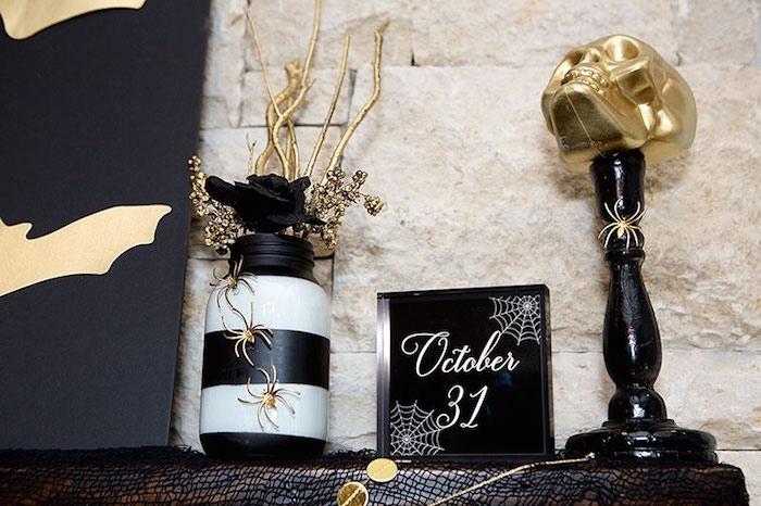 objet deco, salon aux murs en pierre et cheminée noire avec objets décoratifs pour Halloween en or et noir