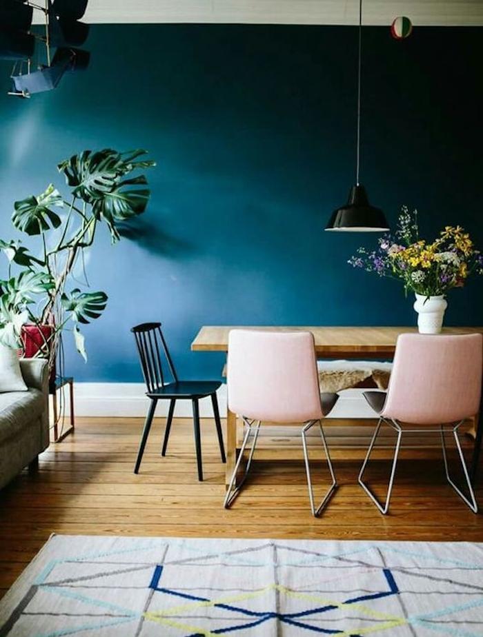 deco salle a manger bleu petrole, table en bois, chaises rose et noir, parquet bois, tapis gris à motifs geometriques, plante verte