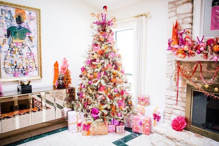 comment décorer un sapin de noel en boules de noel rose et jaunes sur un sapin artificiel blanc, pied en paquets cadeaux, cheminée décorée d une guirlande de noel