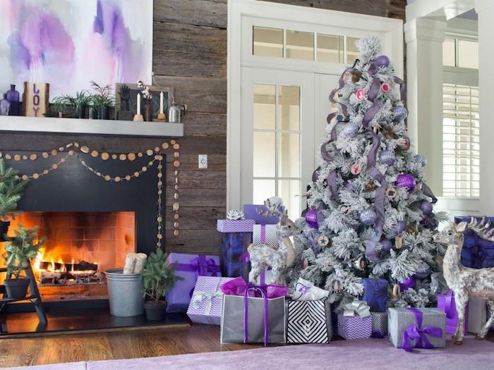 modele de sapin de noel blanc avec decoration de boules de noel et guirlandes mauve, gris et violet, paquets cadeaux gris, cheminée moderne en bois