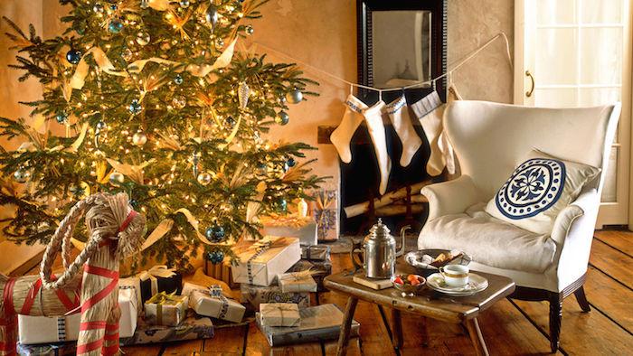 sapin décoré de boules de noel bleues et or et guirlandes lumineuses, parquet en bois brut, cheminée design avec chaussettes blanches accrochées, fauteuil blanc cassé,
