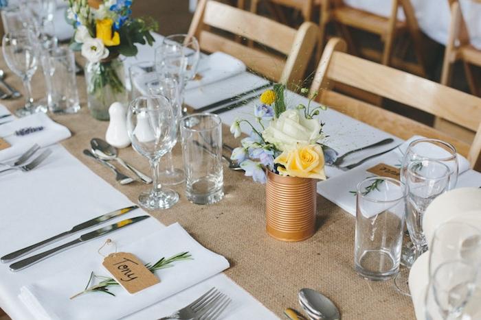 recyclage boites de conserve, table couverte de nappe blanche et toile de jute comme chemin de table. boîtes de conserve repeints et pots en verres avec bouquet champetre