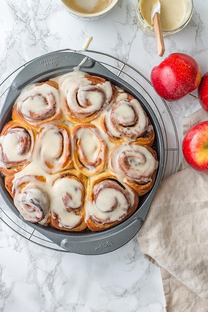 dessert d'automne classique de brioches roulées à la cannelle et aux pommes au glaçage blanc
