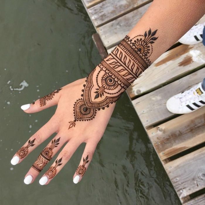 modele henné main, manucure aux ongles blancs, tatouage au henné noir à design ethnique pour femme