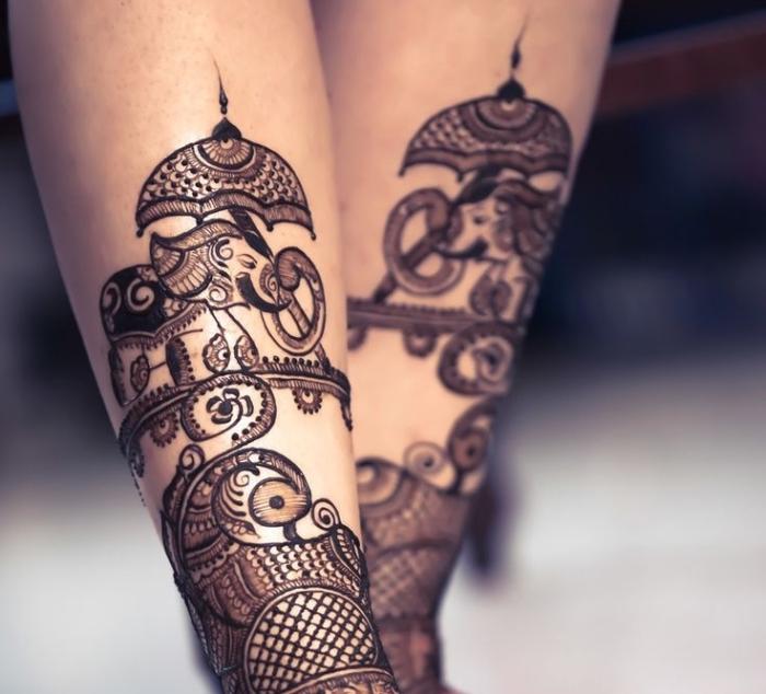 tatouage temporaire, dessin au henné noir sur jambes féminins, tattoo à design ethnique avec petit éléphant et parasol