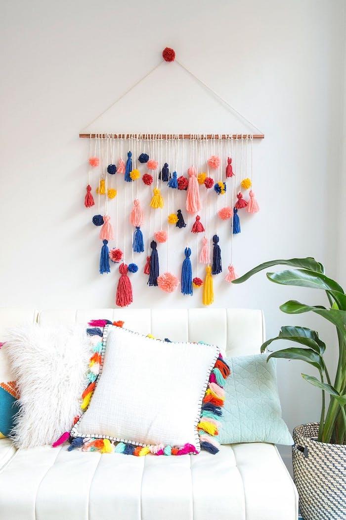diy chambre ado, deco bois flotté, avec des pompons simples et pompons à franges suspendues, canapé blanc avec coussins décoratifs