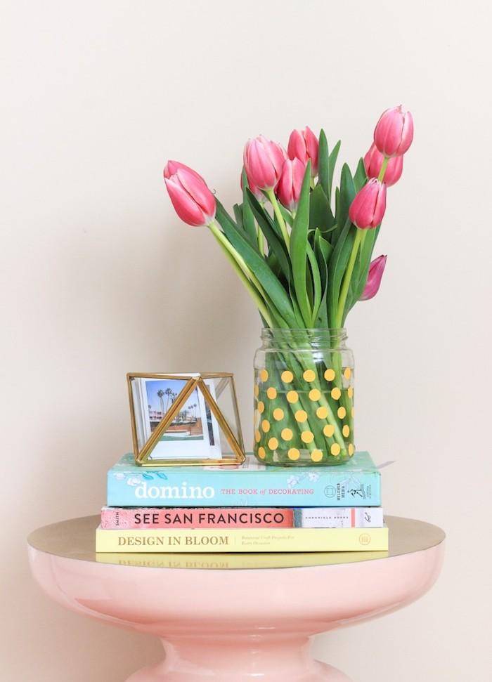 idee creation deco pour la chambre à coucher, un pot en verre décoré de pois jaunes avec un bouquet de tulipes dedans sur une table de nuit rose, livres