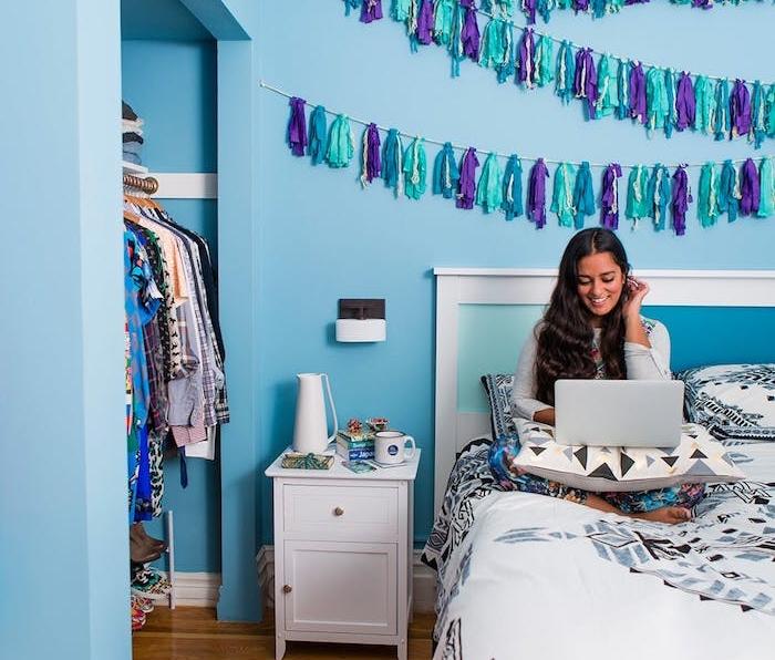 diy chambre ado, exemple de diy deco de pompons à franges bleu et violet sur un mur bleu, dressing pratique, linge de lit à motifs géométriques
