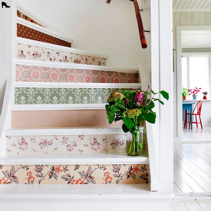 papier peint à motifs floraux et géométriques pour décorer les contremarches d un escalier repeint en blanc, main courante simpe=le en bois, bouquet de fleurs