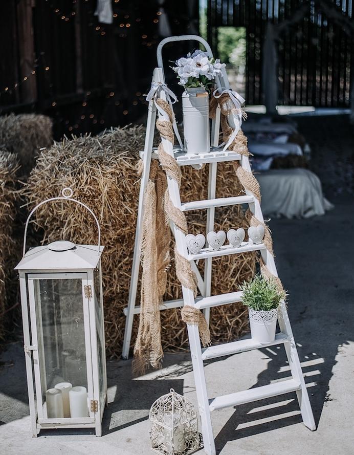 decoration mariage champetre, echelle decorative blanche, coeurs blancs, pot à lait fleuri et grande lanterne avec des bougies à l intérieur, meules de foin