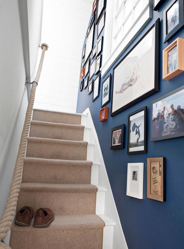 déco montée d escalier, mur repeint en bleu marine avec deco de cades dessins, peintures, photos, tapis beige et main courante en corde, style bord de mer
