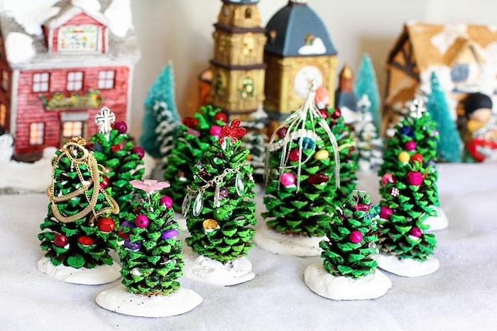 que faire avec des pommes de pin, pommes de pin repeints en vert avec decoration de boules colorées sur une base blanche, activite noel