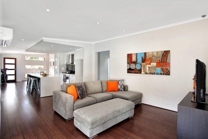 exemple ameangement petite cuisine blanche avec ilot central, tabouret en metal gris, parquet en bois, canapé gris, meuble tv en bois