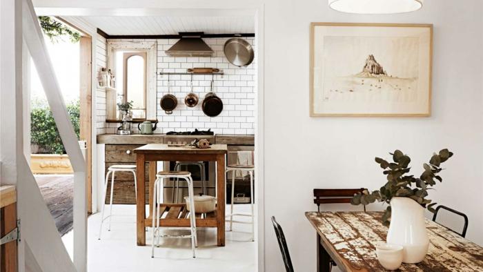 idée comment aménager une cuisine avec bar style rustique, camapagne chic, crédence en carrelage blanc, facade meuble cuisine en bois, ouverture sur salle à manger avec table usée et chaises en bois et métal