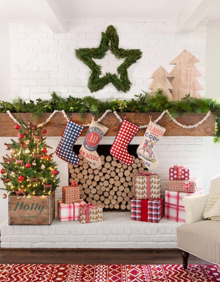 décoration petit sapin de noel de boules de noel rouges et blanches et guirlande lumineuse dans un cagette bois, cheminée rustique en briques en bois avec chaussettes accrochées, étoile et guirlande verte, sapins de noel en bois