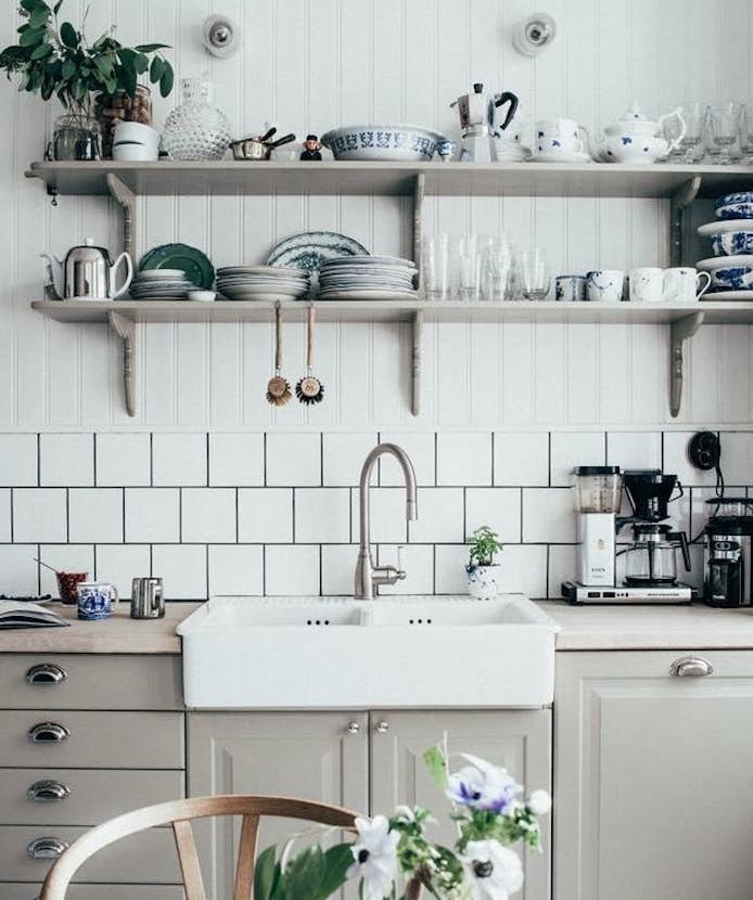 modele de cuisine campagnarde avec façade gri perle, poignées vintage, crédence carrelage blanc, etageres en bois avec vaisselle vintage, plantes vertes