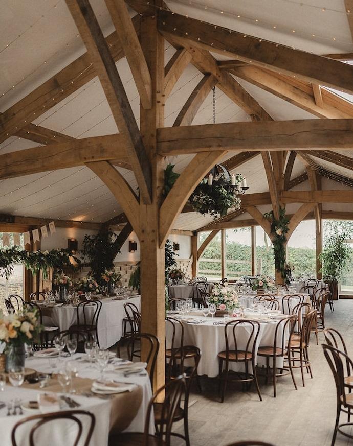 mariage champêtre dans une grange, poutre apparentes, chaises en bois, centre de table floral, chemin de table en jute, nappe blanche