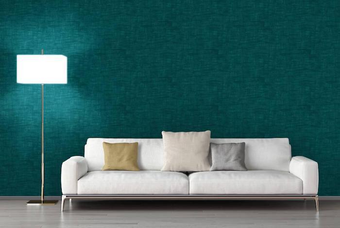 idée de papier peint bleu petrole comme fond d un canapé blanc avec coussin décoratif beige, gris et blanc cassé, parquet clair, parquet grisâtre