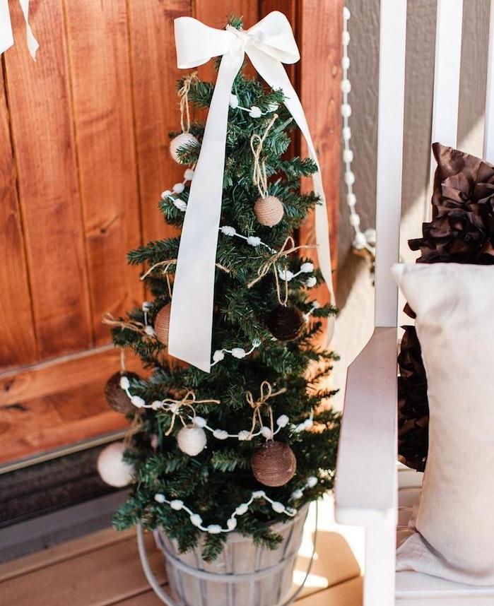 exemple de petit sapin de noel décoré de boules tricot beiges et marron, guirlande blanche diy et pic en ruban blanc