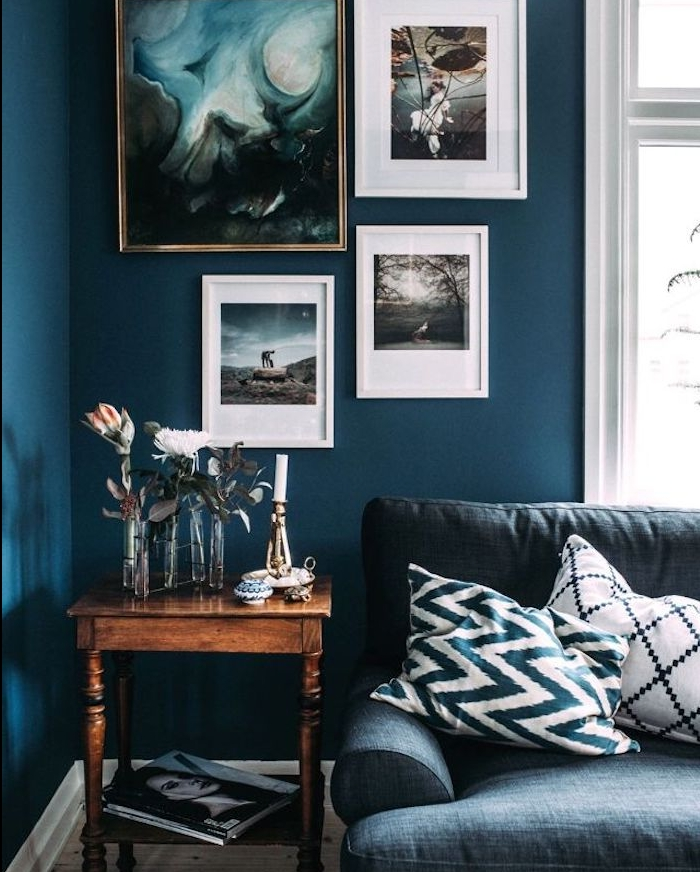 idée de peinture bleu pétrole dans un salon vintage, mur de cadres peinture, table d appoint en bois, canapé bleu gris, déco de soliflores