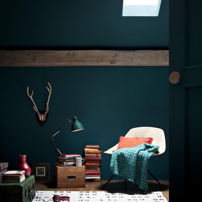 modele d intérieur couleur bleu pétrole, chaise scandinave, pile de livres, coffret vert émeraude, tapis blanc à lettres noires, poutre apparente, deco de bois de cerf