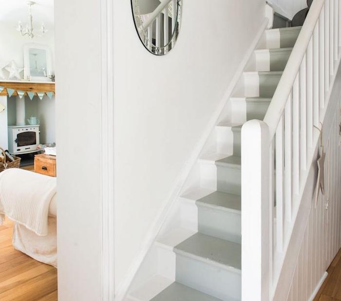 une trompe l oeil, imitation tapis gris sur un escalier repeint, couleur blanche, miroir rond avec cadre metallique, ouverture sur un séjour style shabby campagne, cheminée rustique, canapé blanc
