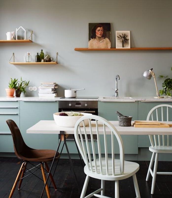 facade cuisine bleu celadon, table salle à manger en noir et blanc, chaises blanches et chaise marron, étagères en bois