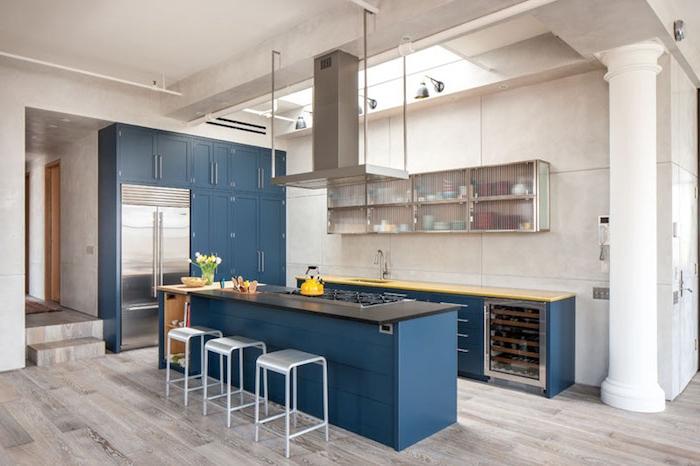 facade cuisine avec ilot central couleur bleu pétrole, parquet clair, aspirateur inox, colonne blanche, design industriel