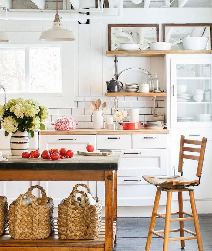 amenagement cuisine campagne chic avec facade meuble cuisine blanc, petites étagères en bois, îlot établi en bois vintage, déco fleurs et légumes