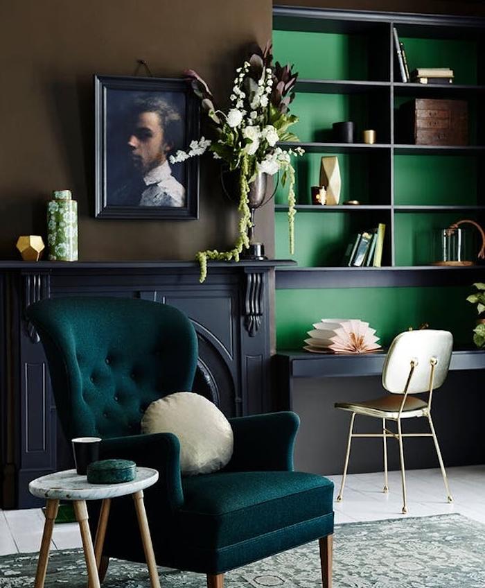 fauteuil couleur bleu pétrole, cheminée grise, bibliothèque avec fond vert, tapis gris et vert clair vintage, portrait peinture cadre retro