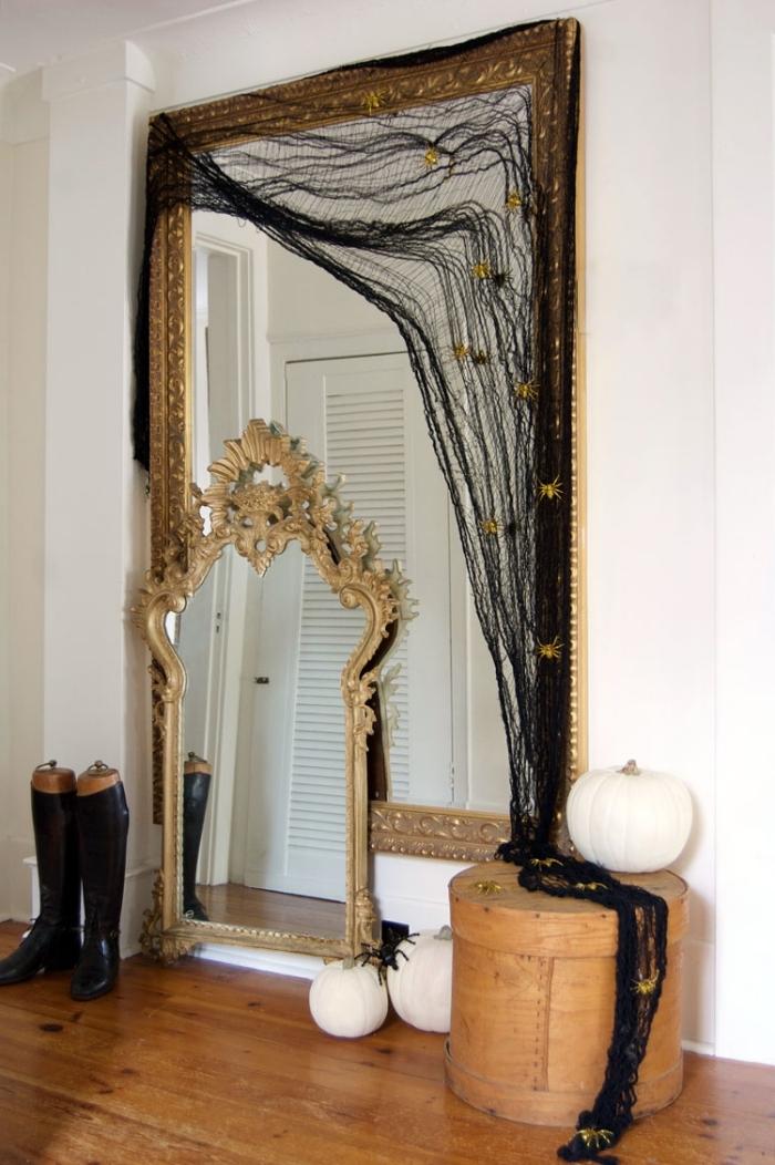activité manuelle halloween, déco chambre à coucher avec grand miroir au cadre doré couvert de tissu noir comme toile d'araignée