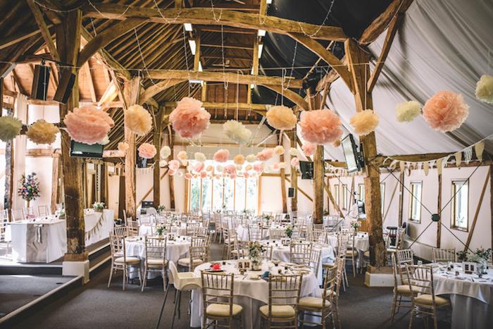 mariage champetre chic dans une grange, fleurs en papier de soie blanches et roses suspendues, poutres apparentes, tables decoration simple