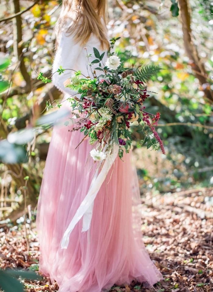 exemple de fleurs mariage champetre, bouquet coloré, femme en top blanc et jupe rose, cadre forestier