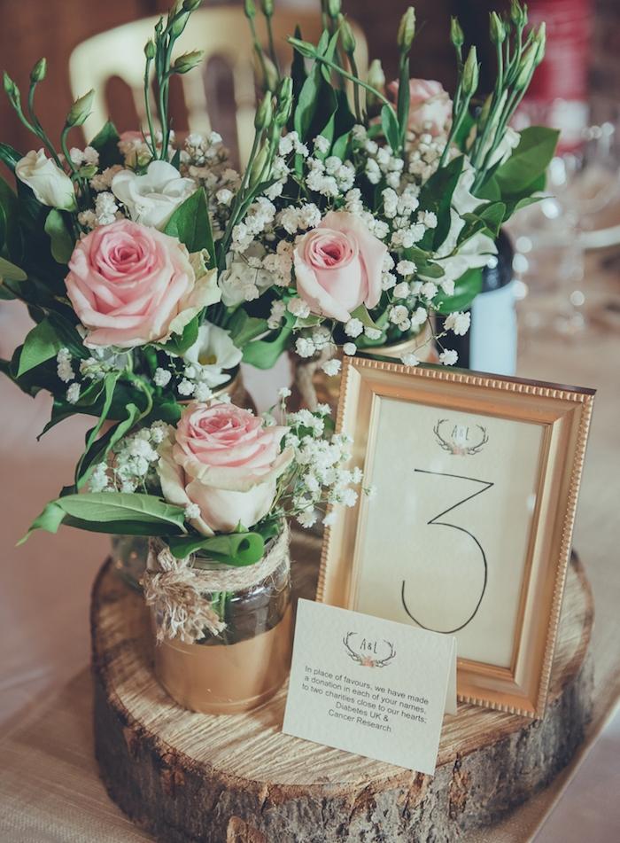 deco table mariage, style champetre, idée de diy mariage, rondin en bois, avec pot en verre repeint couleur or, bouquet de rose et muguets, cadre doré, chiffre de table