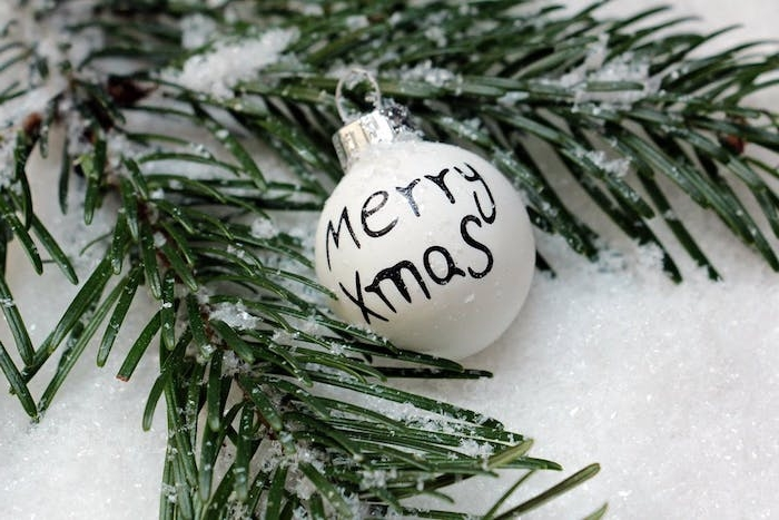 fond d écran de noel en branches de pin enneigées, boule de noel blanche, décorée de message joyeux noel
