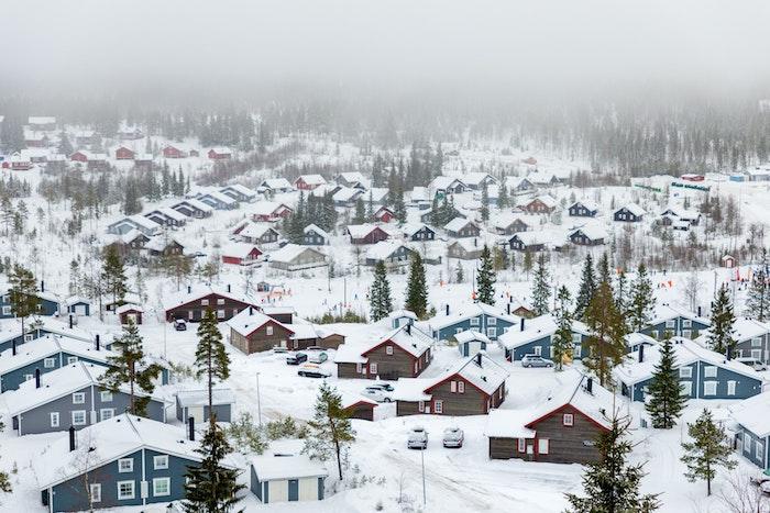 fond d écran hiver, village enneigé au peid d une montagne en suede, maisons cabanes bleues, marrons et rouges