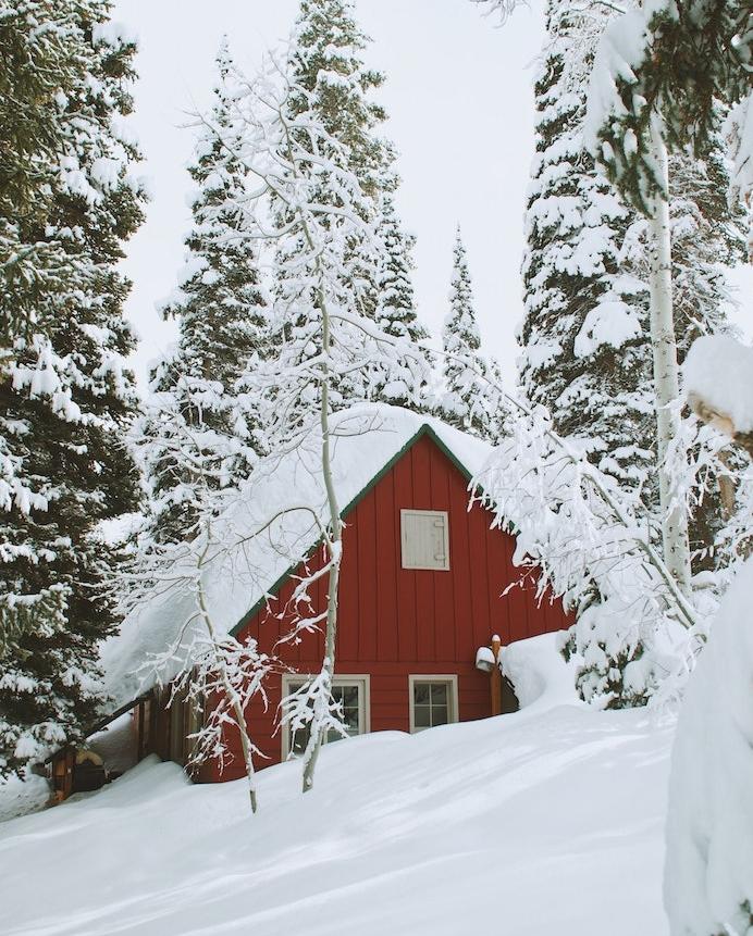 fond ecran paysage hiver avec une maison cabane ensevelie sous la neige, arbres conifères, sapins couverts de neige