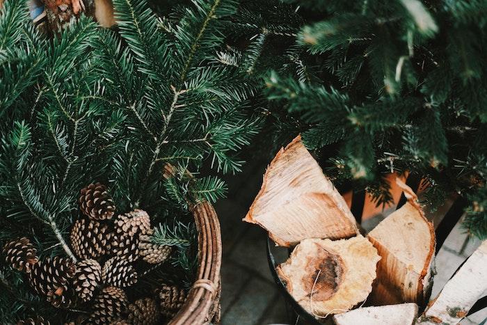 fond d écran hiver en branches de conifères et pommes de pin, bois pour cheminée pour une ambiance chaleureuse