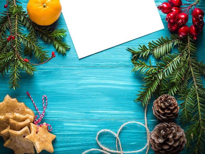 fond d écran de noel simple en branches de pin, biscuits, pommes de pin, houx, orange et feuille blanche sur un fond bleu