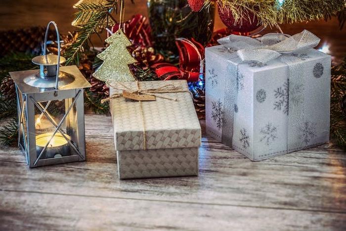 fond noel pour votre ecran, lanterne grise avec une bougie a l interieur, cadeaux avec emballage festif sous u sapin de noel décoré