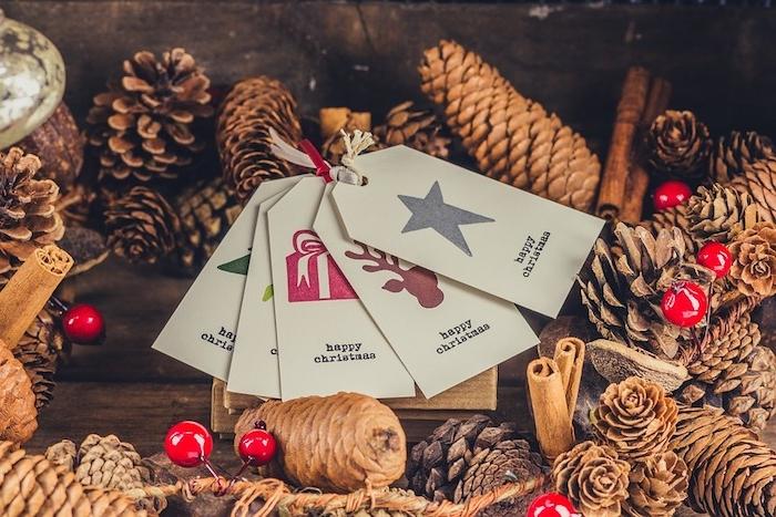 fond d écran de noel en pommes de pin, cannelle, houx et étiquettes cadeaux sur une table en bois