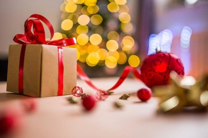 fond noel en cadeau en papier kraft, décoré de ruban rouge, boule de noel rouge et sapin de noël illuminé de guirlandes lumineuses