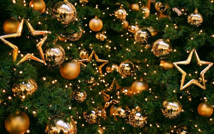 fond noel en sapin de noel décoré d ornements dorés, boules de noel et étoiles en or et guirlande lumineuse