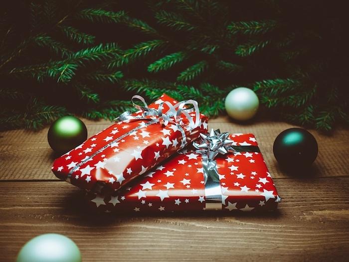 fond d ecran de noel, cadeau avec emballage rouge à étoiles blanches, branches de pin vertes et boules de noel vertes sur une surface en bois