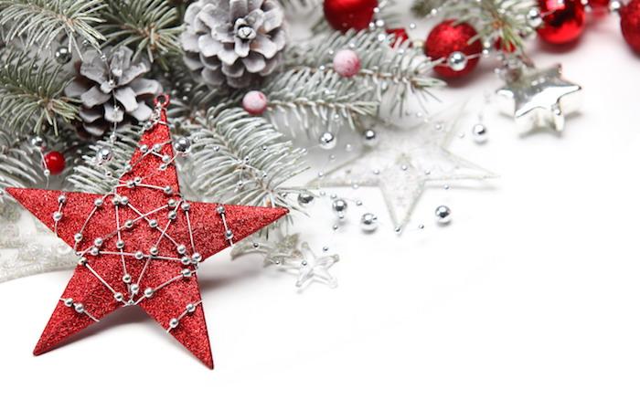 fond ecran noel en étoile rouge décorée d une guirlande de perles argentés, branches de pin enneigées, pommes de pin et boules de noel