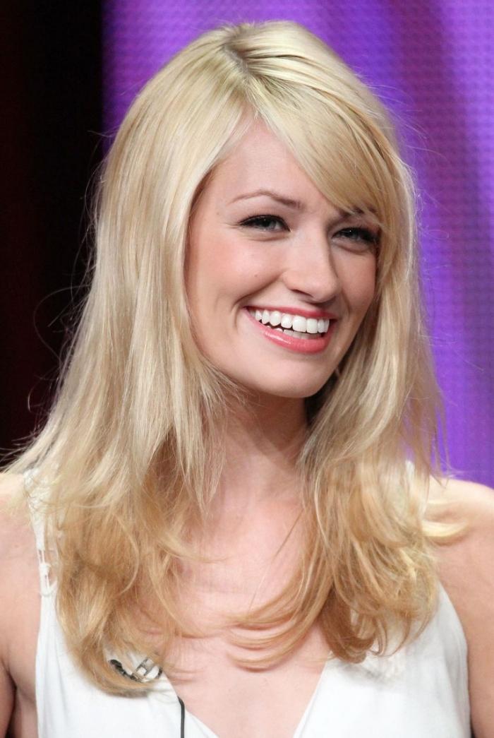 coiffure célébrité de Beth Behrs, femme aux cheveux longs blonds, coiffure féminine avec frange de côté