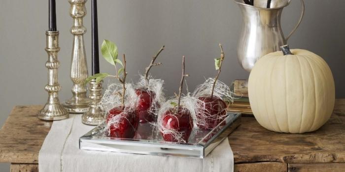 table en bois massif avec desserts pommes rouges sucrées et citrouille blanche, modèle de bougeoir noir et or