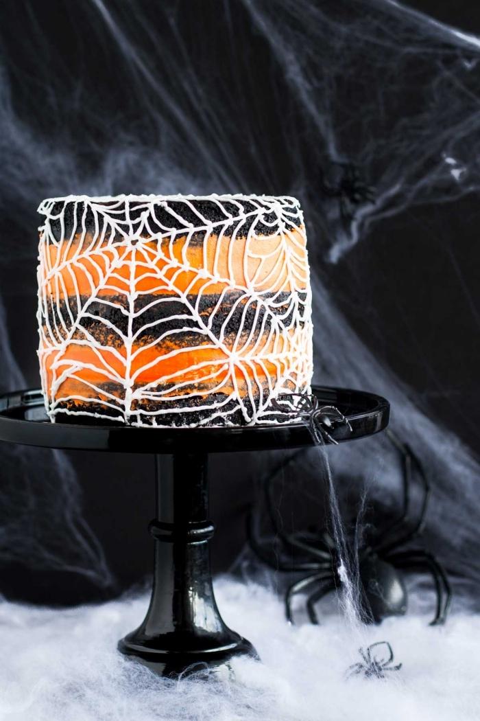 fete halloween, idée pour un gâteau style Halloween au glaçage rayé en orange et noir avec décoration sucrée en forme de toile d'araignée