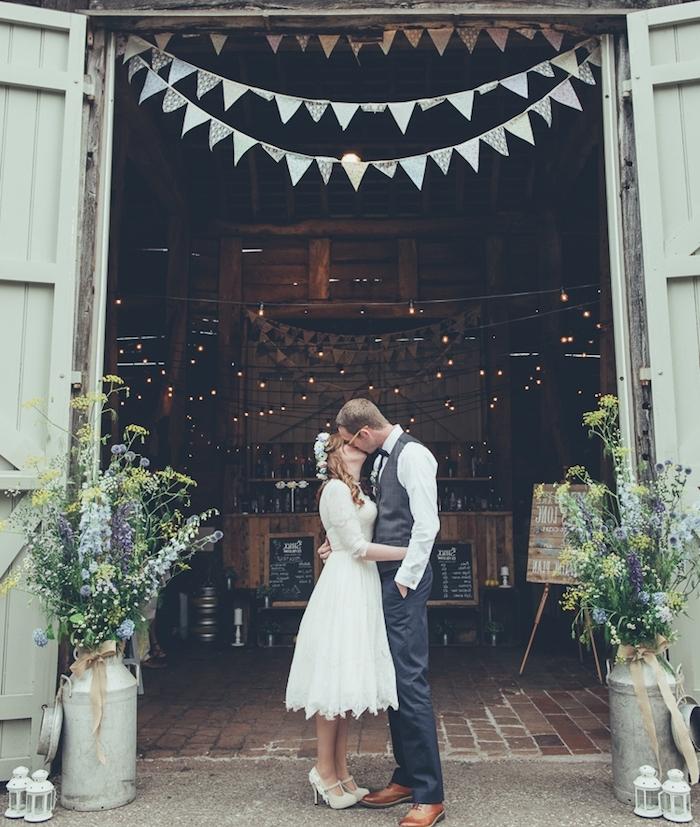 mariage champetre dans une grange, guirlande fanions, couple mariés, lanternes blanches et pots à lait fleuris, guirlande lumineuse