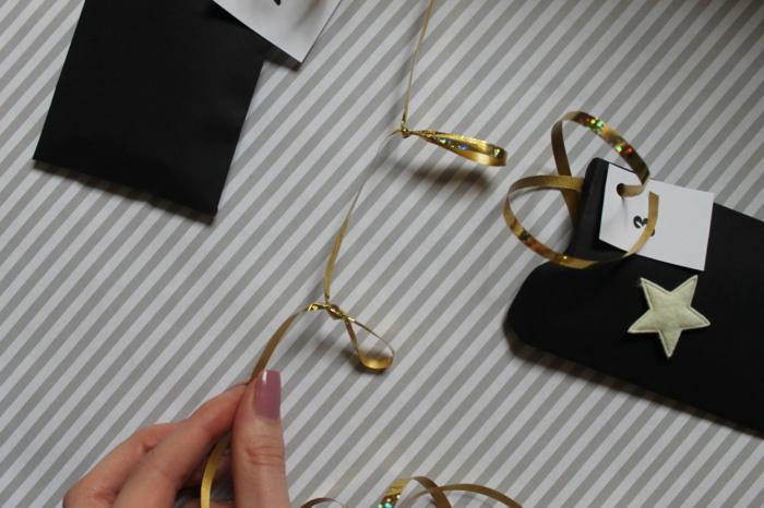 guirlande de cadeaux en sacs de papier noirs et ruban noir, idées de Noel festives